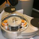 Litewski gramofon Reed Muse 3C wyposażono w dwa typy napędu: konwencjonalny - paskowy - oraz frykcyjny. Ten drugi polega na obracaniu osi napędowej talerza przez dwie umieszczone po jej obu stronach rolki o różniej średnicy (pomarańczowe elementy na zdjęciu). Każda rolka ma własny napęd bezpośredni, przekazywany przez silnik. Rolki dotykają krawędzi głównego talerzyka i kręcąc się, wprawiają go w ruch obrotowy. Ewentualne drgania i nierównomierności zostają zniwelowane przez precyzyjną kontrolę obrotów oraz geometrię układu. Sam talerz jest dosyć ciężki, co poprawia bezwładność. Producent deklaruje, że Muse 3C z napędem frykcyjnym brzmi bardziej atrakcyjnie. Gdyby to komuś nie odpowiadało, w kilka minut i bez żadnych dopłat może wrócić do paska. Muse 3C kosztuje 16000 euro. Reed oferuje także trzy typy ramion, po około 2000 euro każde.